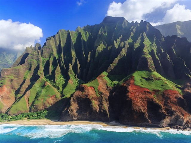 On the island of Kauai, also known as the Garden Isle, you can explore the famed Na Pali Coast. Along the coast, sheer cliffs covered in lush, green vegetation drop off rapidly, meeting the sands of private, secluded beaches. The scenery is unlike anything else on the planet. Many visitors recognize the landscape because the Na Pali Coast served as a primary filming location for Jurassic Park and several other movies. You can hike among the cliffs if you head for the trails in the Na Pali Coast State Park. If adventure calls, there are some cliffs where locals can show you how to safely jump into the water below.