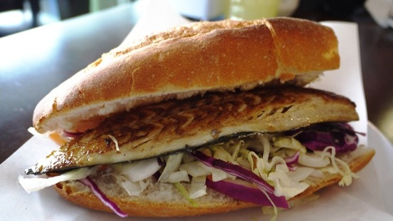 A popular street food from Istanbul, especially in the Eminönü neighborhood, balık ekmek is a freshly grilled fish fillet packed in half a loaf of white bread with plenty of onions, tomatoes, salad, and herbs.